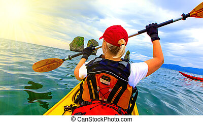 Woman paddles kayak on Pacific ocean