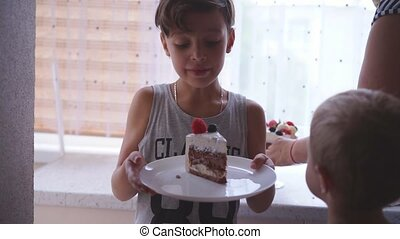 The woman puts the cake in the dish to children