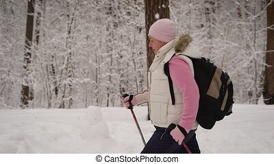 The woman quickly goes through the snowy forest. She falls a...
