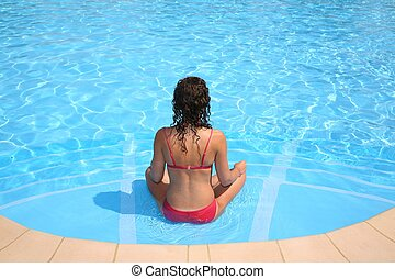 The woman relaxs at pool