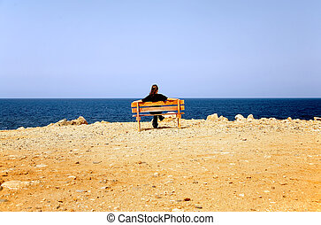 The woman sits on a bench at coast