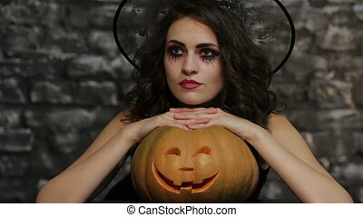 The woman-sorceress posing with pumpkin - The woman in the...