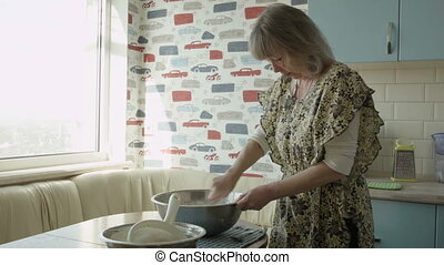 The woman stirs the dough, takes a rag, wipes the table