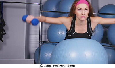The woman trains on fitball