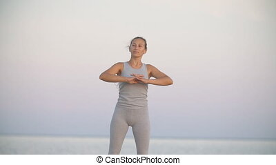 the woman twists her head doing thereby exercises for the...