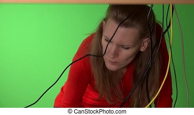 The woman under the table tries to find the right cable for her computer. 4K
