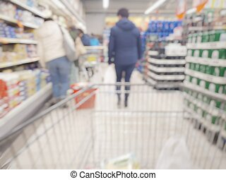 The woman walks inside in supermarket. Abstract blurred background.