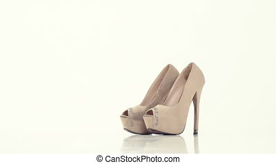 woman wears beige shoes with high heels - the woman wears...