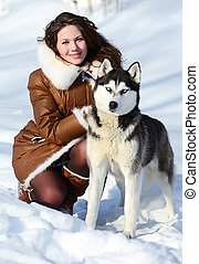 The woman with a dog Husky in the winter