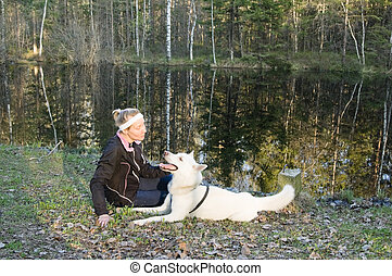 The woman with a dog on the bank of wood lake