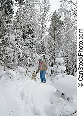 The woman with a dog on walk in a winter wood