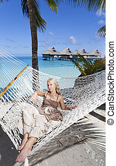 woman with blonde long hair in  long dress  lies in a hammock on background of the sea