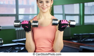 The woman with dumbbells in sports club gym