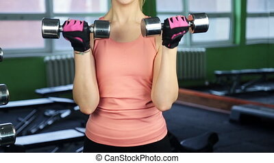 The woman with dumbbells in sports club