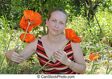 The woman with red poppies in a garden.