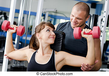 The woman with the trainer in sports club