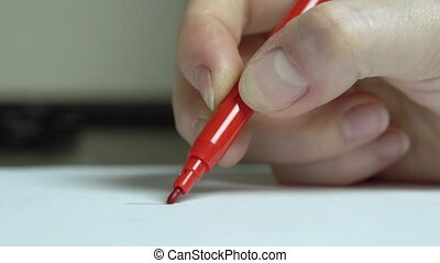 The woman's hand draws a red line with a felt-tip pen on...