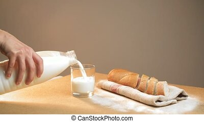 The woman's hand pours milk into a siper glass on the table. The concept of a quick breakfast