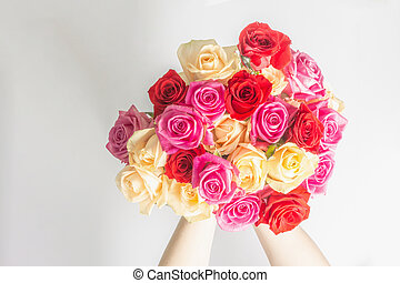 The woman's hands are holding a beautiful bouquet of fresh multicolored roses