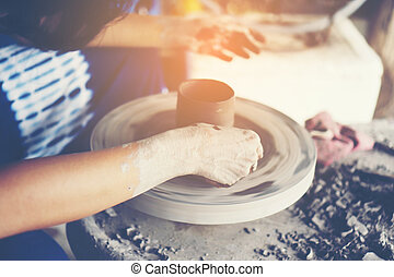 The woman's hands close up, the masterful studio of ceramics works with clay on a potter's wheel