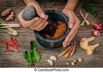The Women hold pestle with mortar and spice red curry paste...