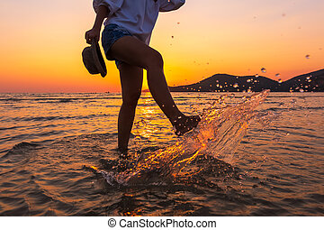 the women play water splash on the beach between sunset