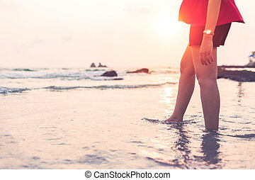 the women walking on the beach in the water between sunset.