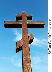 The wooden cross on a blue sky background