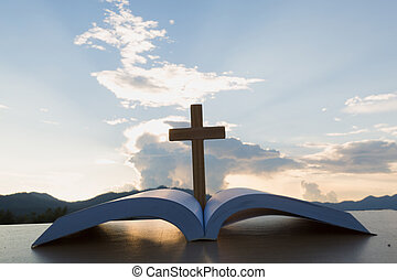 The wooden cross over opened bible on wooden table, Beautiful sky background