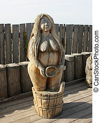 The wooden figure of a woman on the background fence.