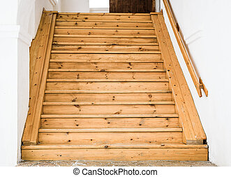 wooden staircase and railing against white walls