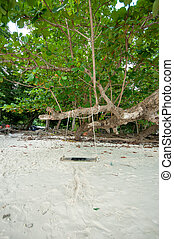 the wooden swing on a beach