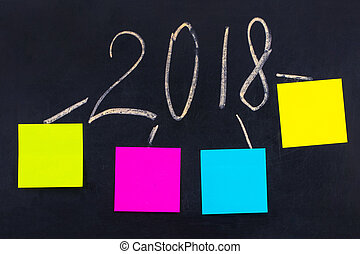 The word 2018 written on the blackboard with blank notes. New year goals or resolutions