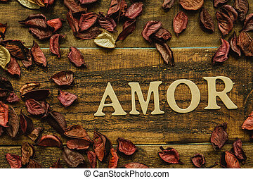 "The word ""Amor"" on a rustic wooden with dry red petals..."