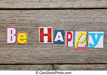 The word be happy in cut out magazine letters