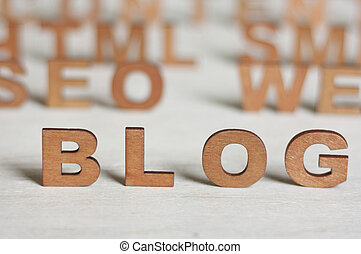 the word blog with wooden letters on a background of blurred letters