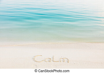 The Word Calm Written in the Sand on a Beach with blue sea background