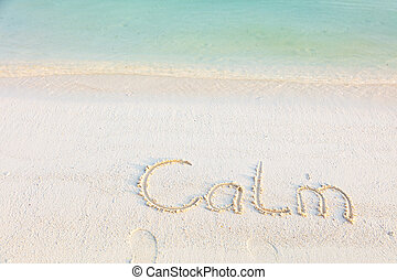 The Word Calm Written in the Sand on a Beach with morning sea background