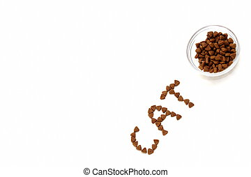 The word CAT is laid out with dry cat food on a white background next to a bowl of cat dry food.