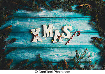 The word Christmas on a blue wooden background.
