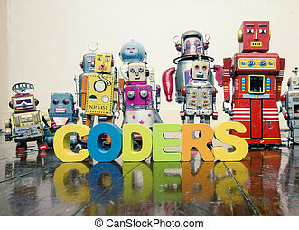 the word CODERS with wooden letters and retro toy robots on an old wooden floor