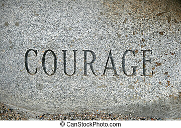 courage - the word courage carved onto a granite cobble...