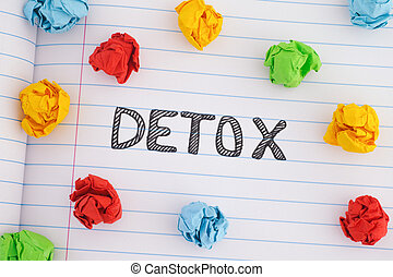 The word Detox on notebook sheet with some colorful crumpled paper balls around it