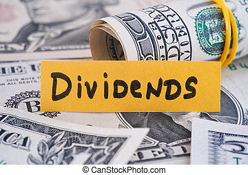 The word Dividends and dollar bills