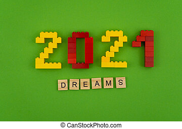 The word dreams 2021 is lined with wooden letters on a green background. Figures from the constructor top view. Postcard in place for text. Flatlay. Yellow and red numbers. Copy space.