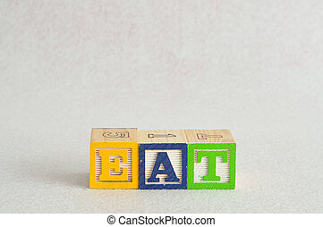 The word eat spelled with alphabet blocks isolated on a white background