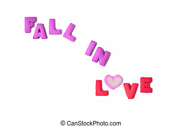 The word FALL IN LOVE spelled with purple and pink alphabet shaped biscuits and a heart shaped marshmallow candy on white background