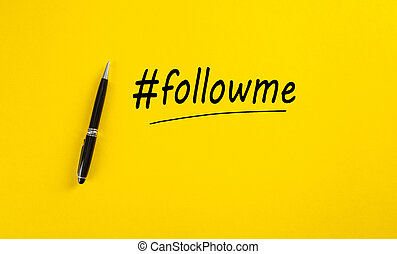 The word follow me or hashtag followme hand written with a black marker pen on yellow background.