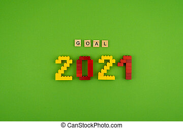 The word goal 2021 is lined with wooden letters on a green background. Figures from the constructor top view. Postcard in place for text. Flatlay. Yellow and red numbers. Copy space.