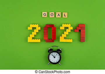 The word goal 2021 is lined with wooden letters on a green background. Small black alarm clock. Figures from the constructor top view. Postcard in place for text. Flatlay. Yellow and red numbers.